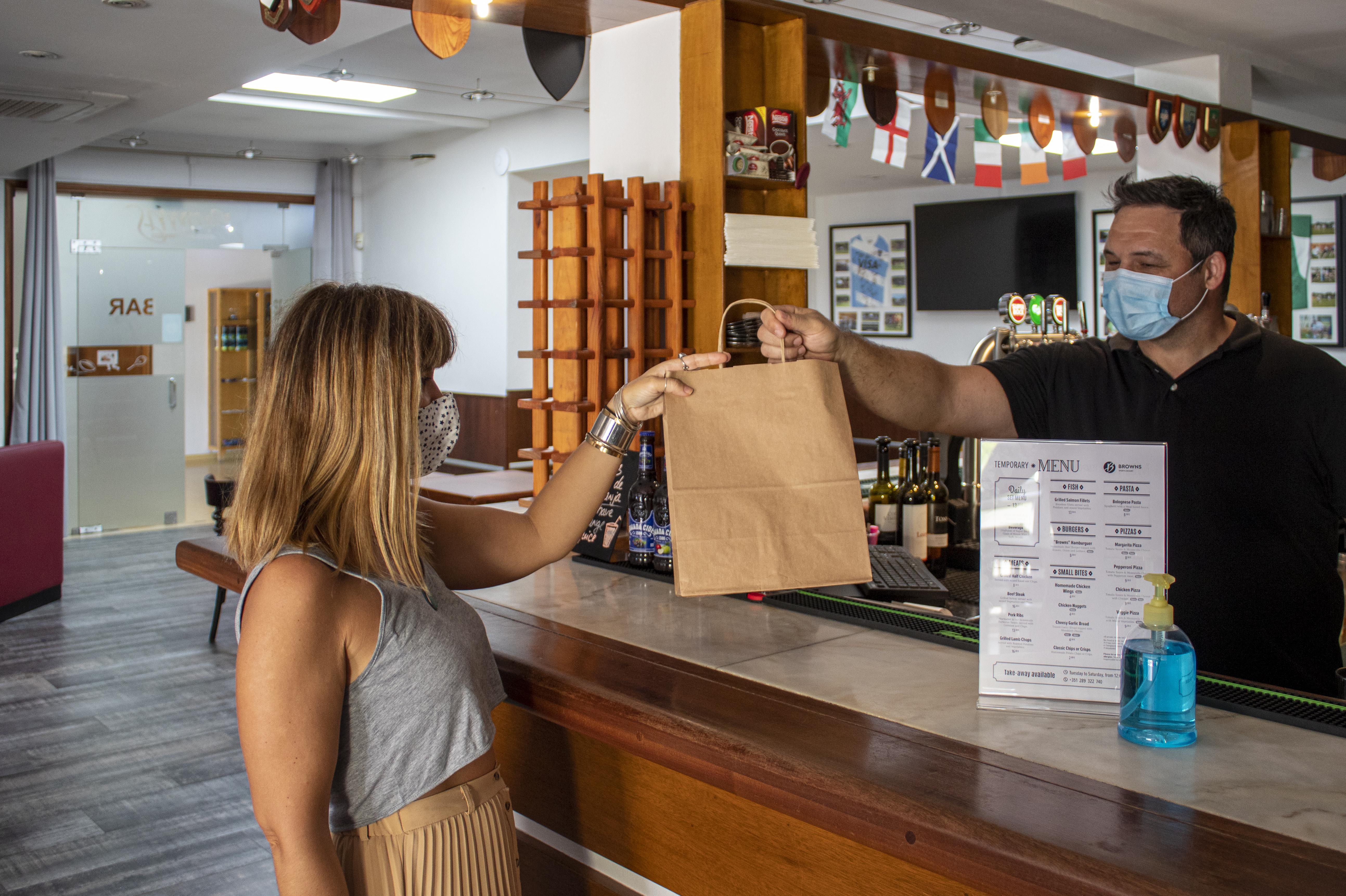 Mulher encomenda comida take-away no Sports Bar & Restaurante.
