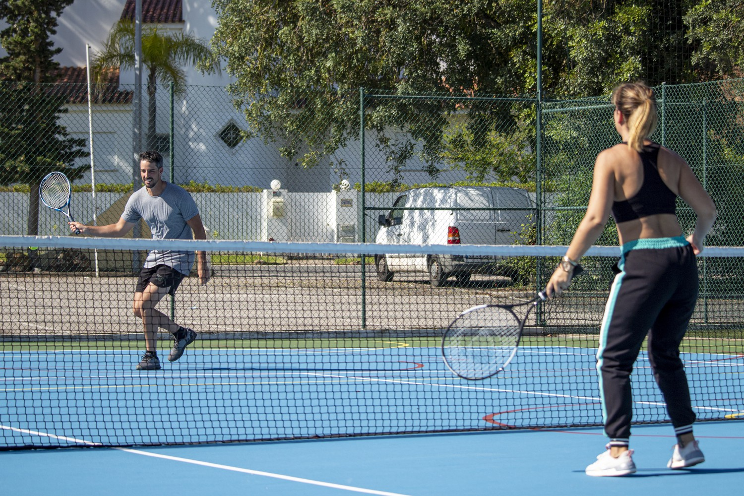 A couple have a good time playing tennis.