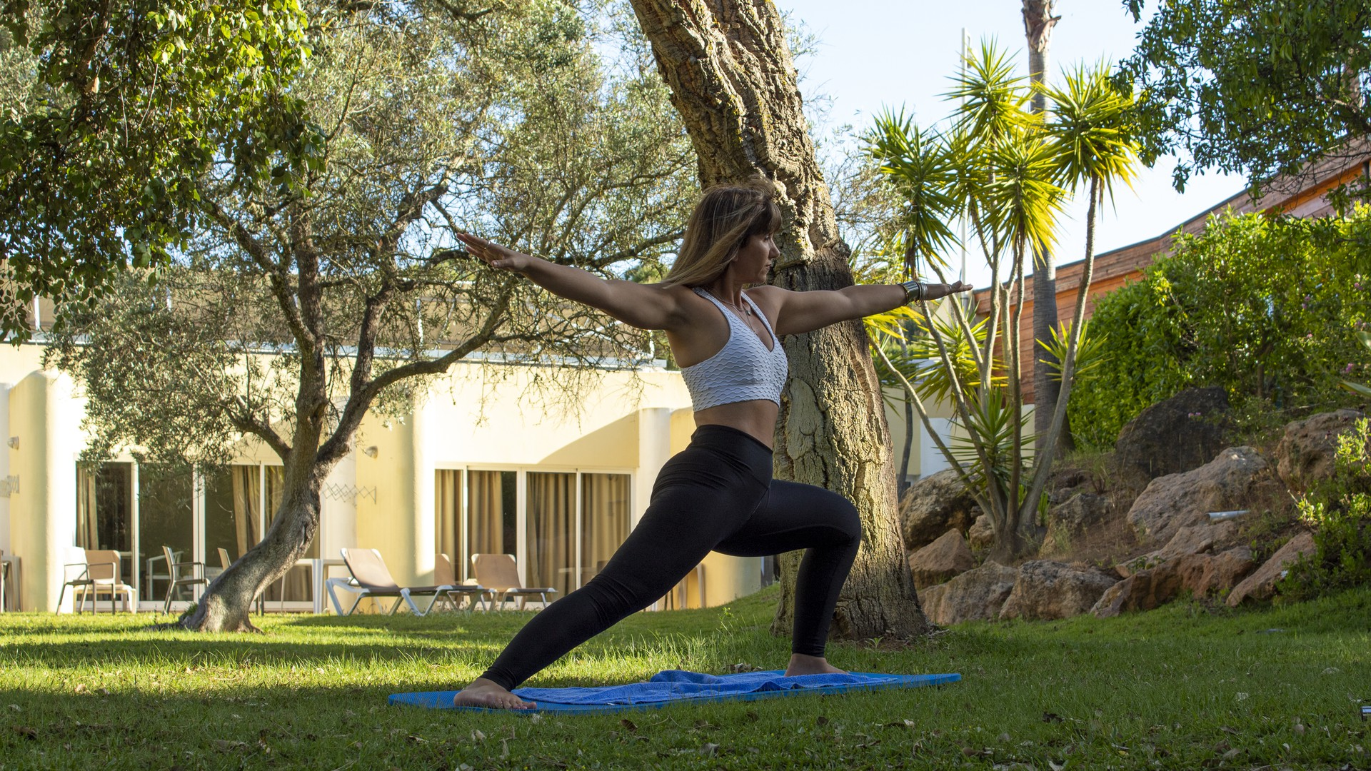 Woman does pilates exercises in a grassed area of her accommodation.